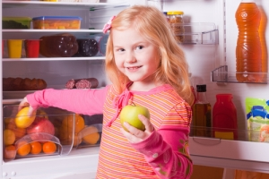 Young girl outside of organized fridge.