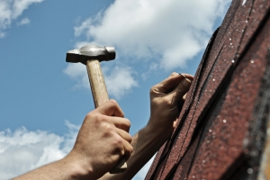 Hammering nail into roof tile